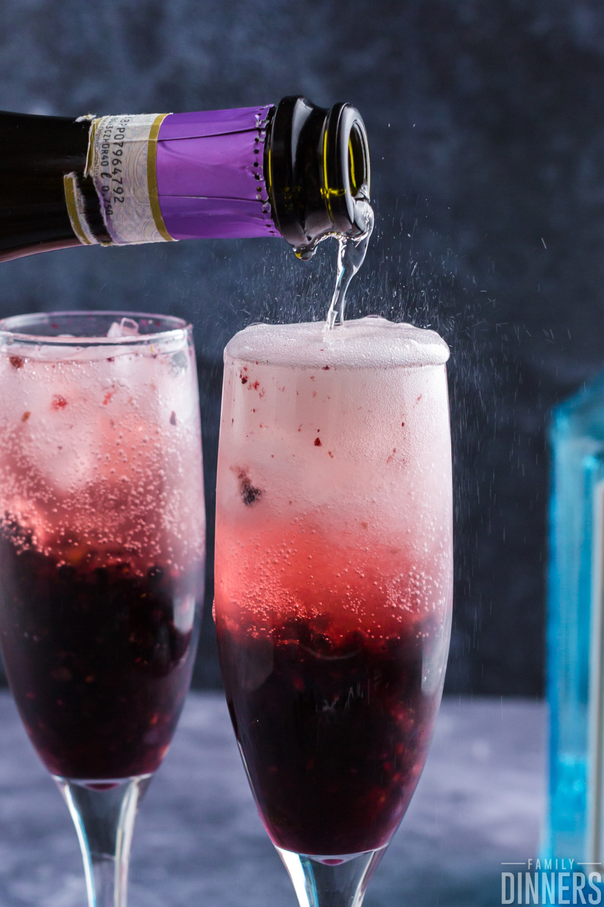 two champagne glasses with blackberry drink inside. Darker blackberry color on the bottom of the glass and light translucent blackberry color at the top. Each glass has fresh thyme and a blackberry on top. Lots of bubbles inside the glass.