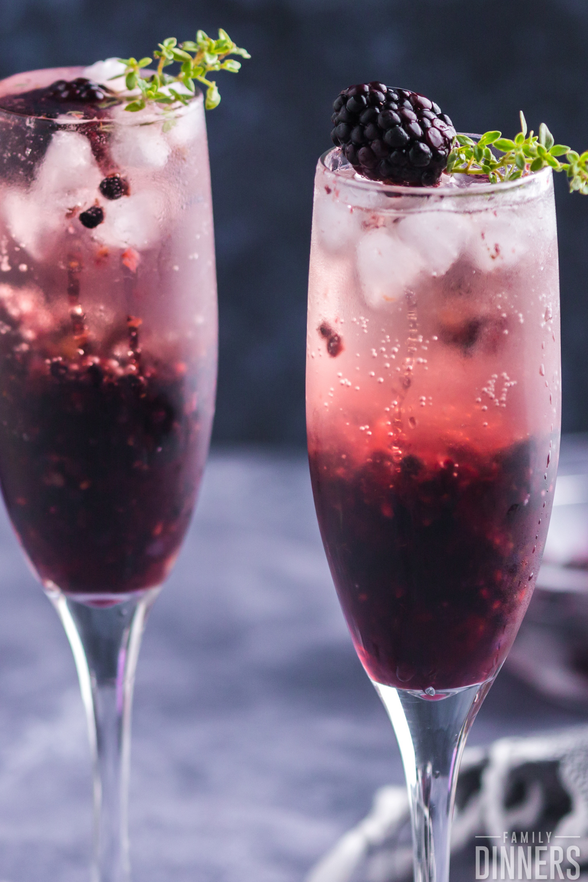 photo of two champagne glasses filled with blackberry cocktail that's dark purple on bottom and lighter pink on top.