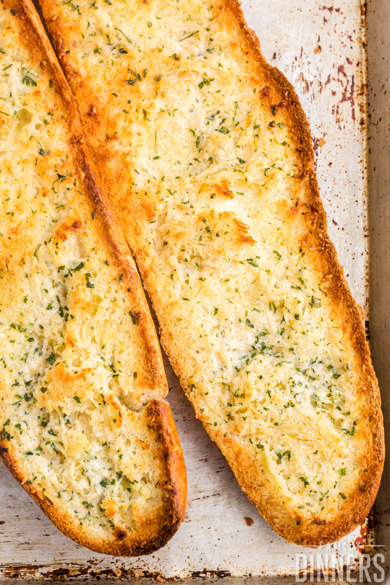 2 halves of a french bread open and toasted with garlic and parmesan