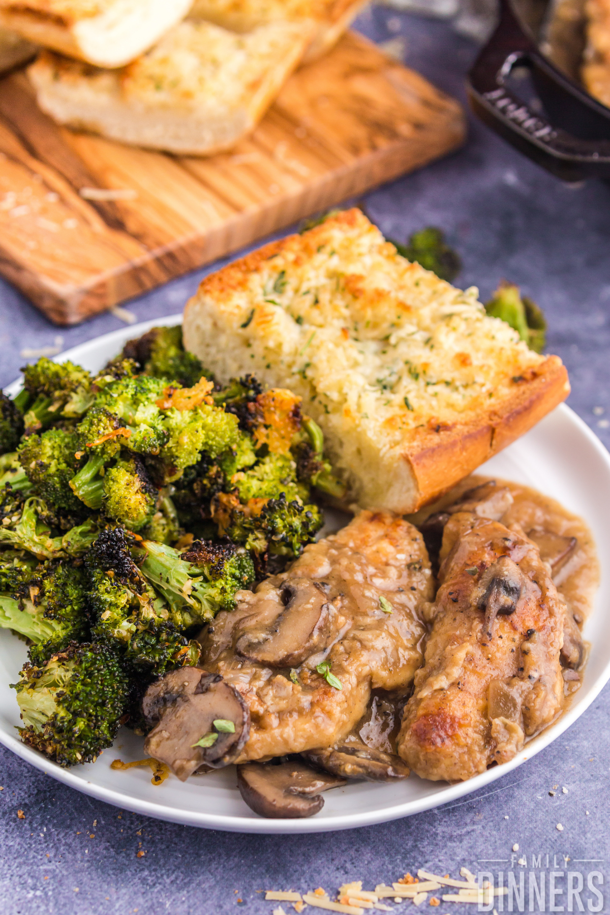 white round plate on blue counter. Plate has two pieces of golden browned chicken with mushrooms and sauce as well as crispy parmesan roasted broccoli and garlic cheese bread slice.