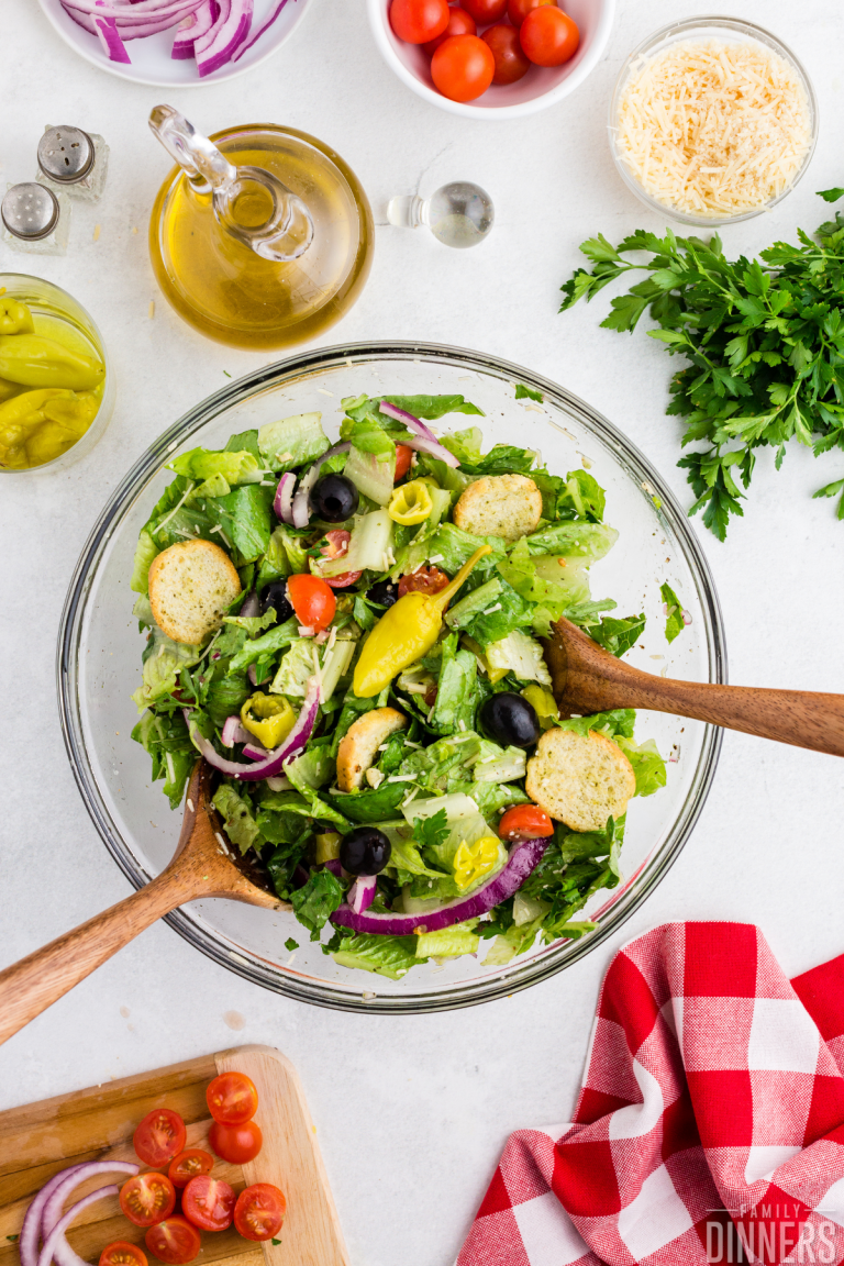 italian salad in a bowl with wood salad utensils