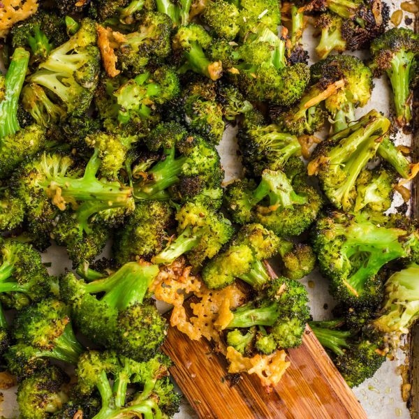 baking sheet with parmesan roasted broccoli on top and wooden spatula