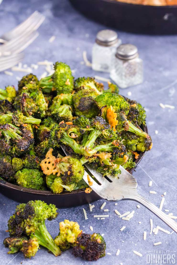 cast iron pan piled high with roasted broccoli, fork scooping broccoli