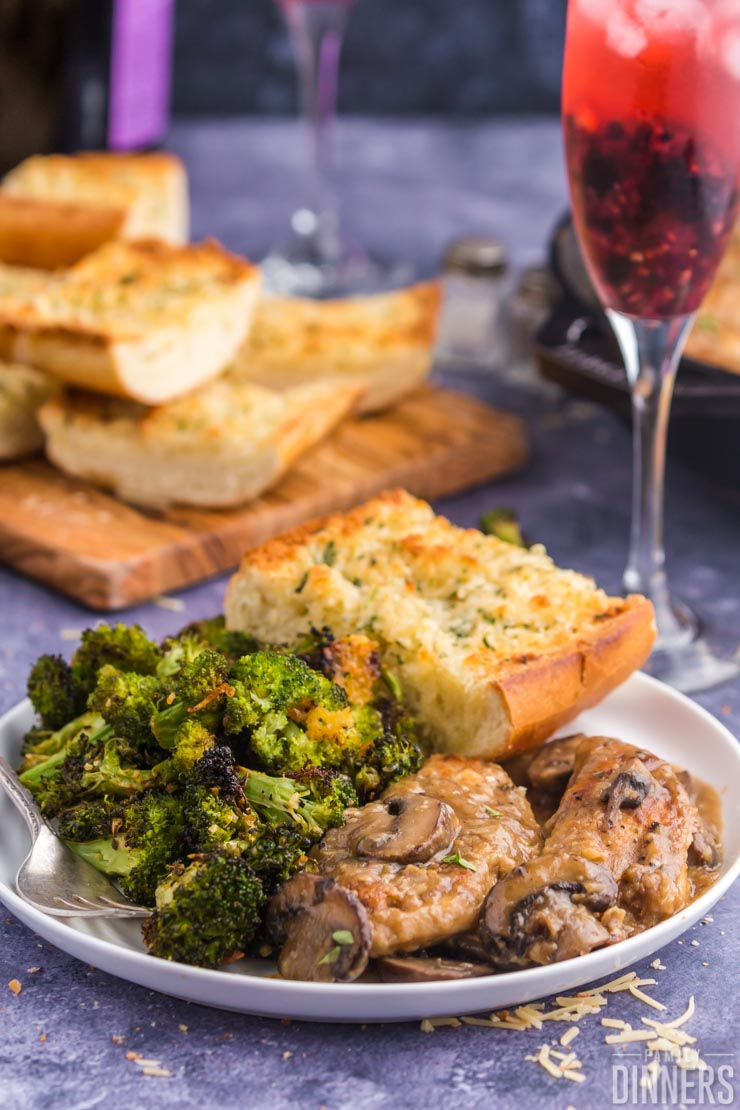 broccoli, french bread, and chicken on white plate, french bread and champagne glass in background