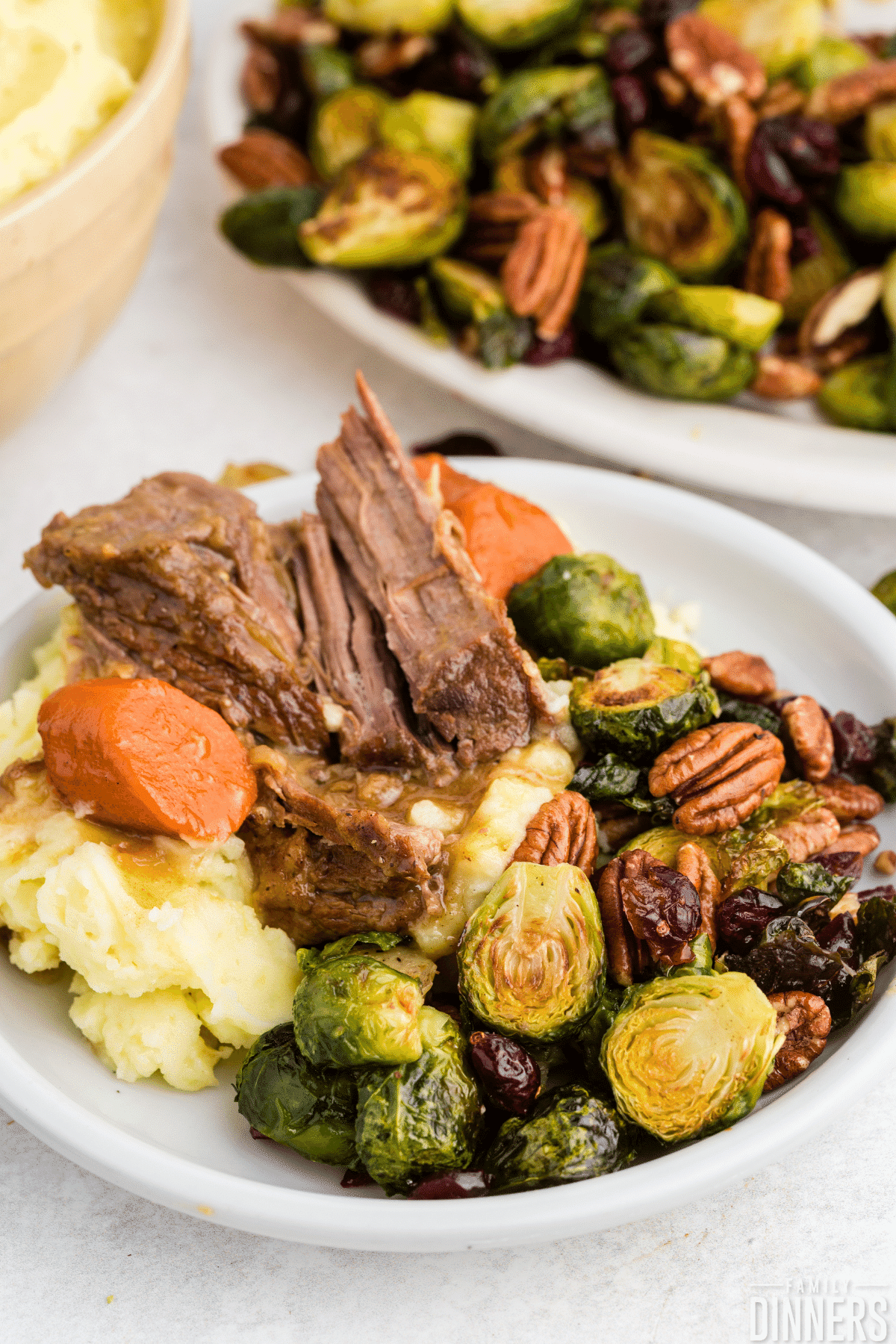 pot roast on a bed of mashed potatoes, carrots and brussels sprouts