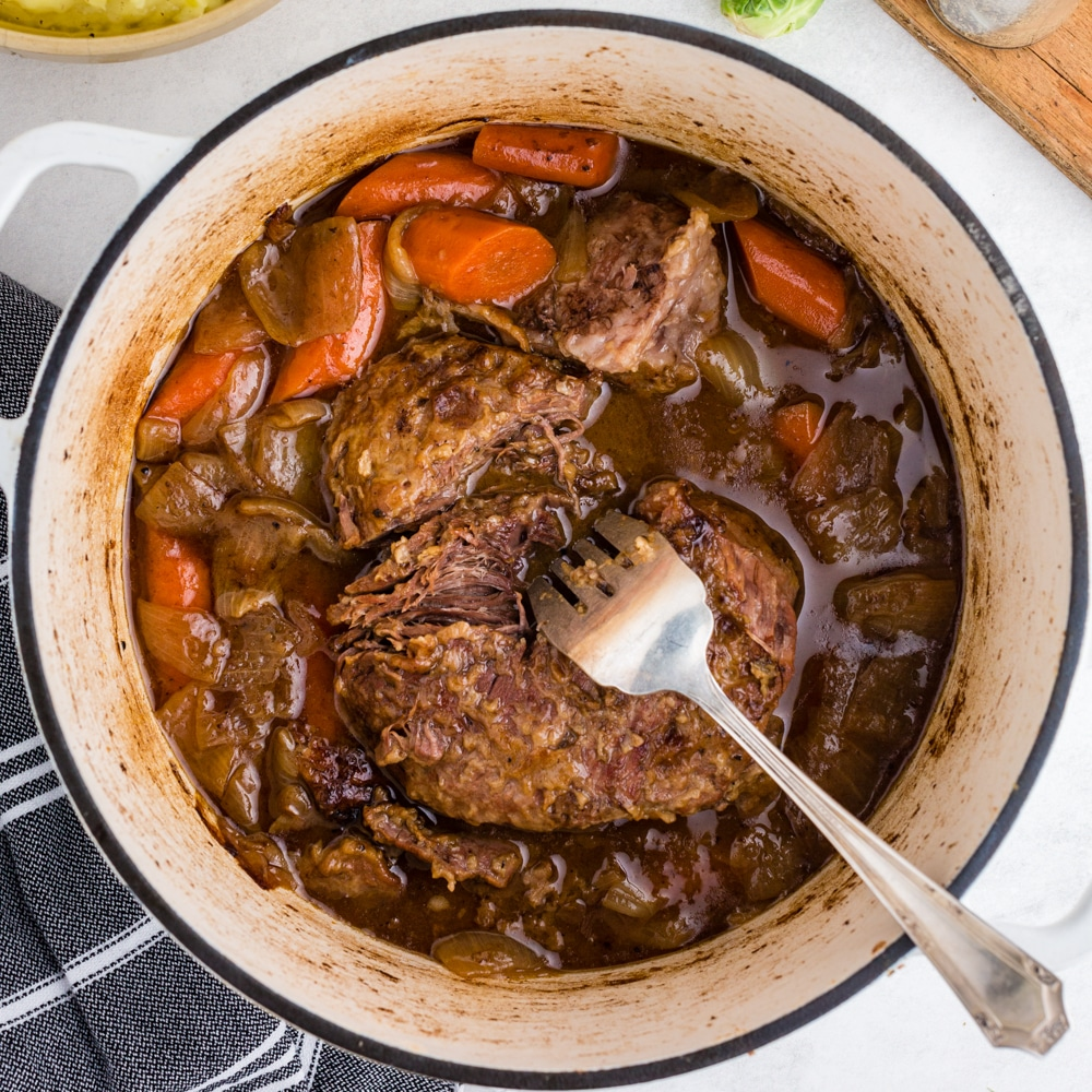 overhead view of cooked pot roast and carrots in white dutch oven