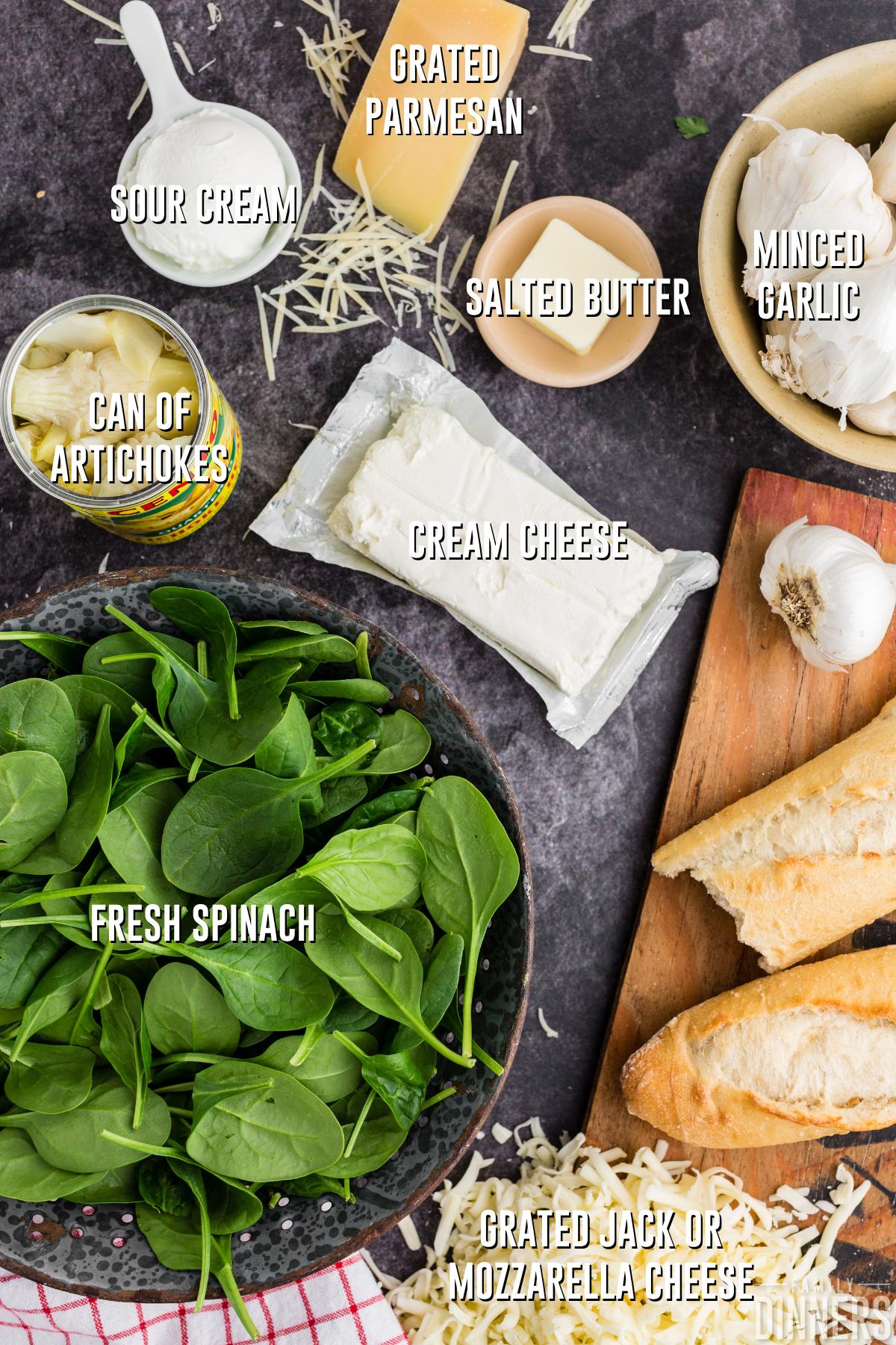 spinach artichoke dip ingredients on dark gray counter