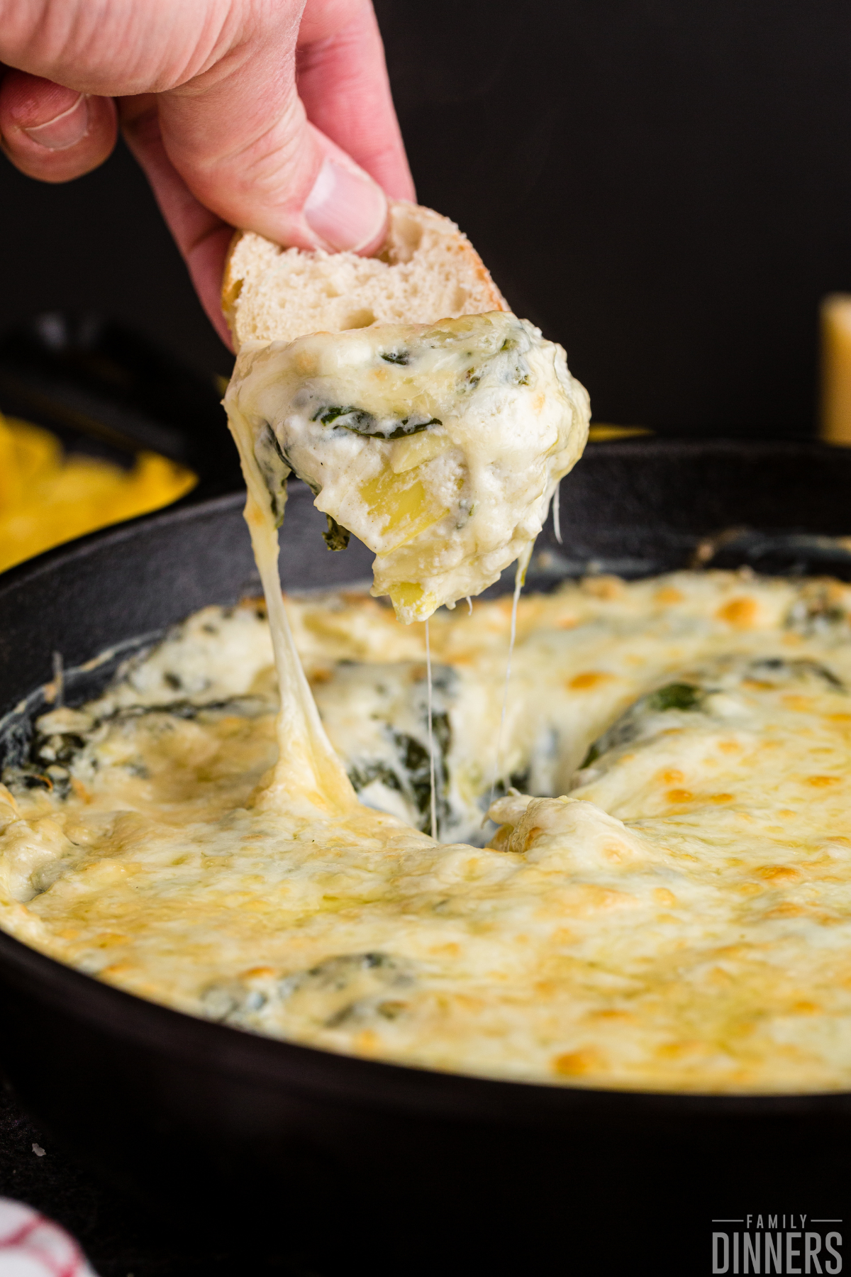 Chip being dipped into gooey spinach and artichoke dip that's very cheesy
