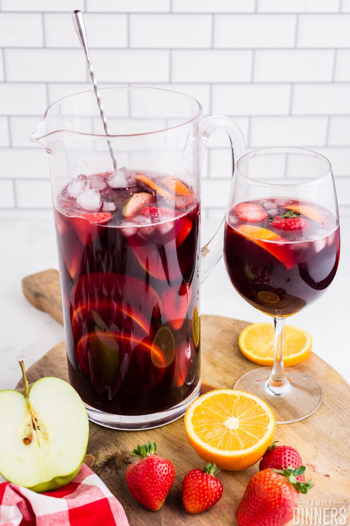 large glass pitcher with silver swizzle stick full of red wine sangria and chopped up fruit next to wine glass full of red wine sangria and fruit. Cut fruit on chopping board.