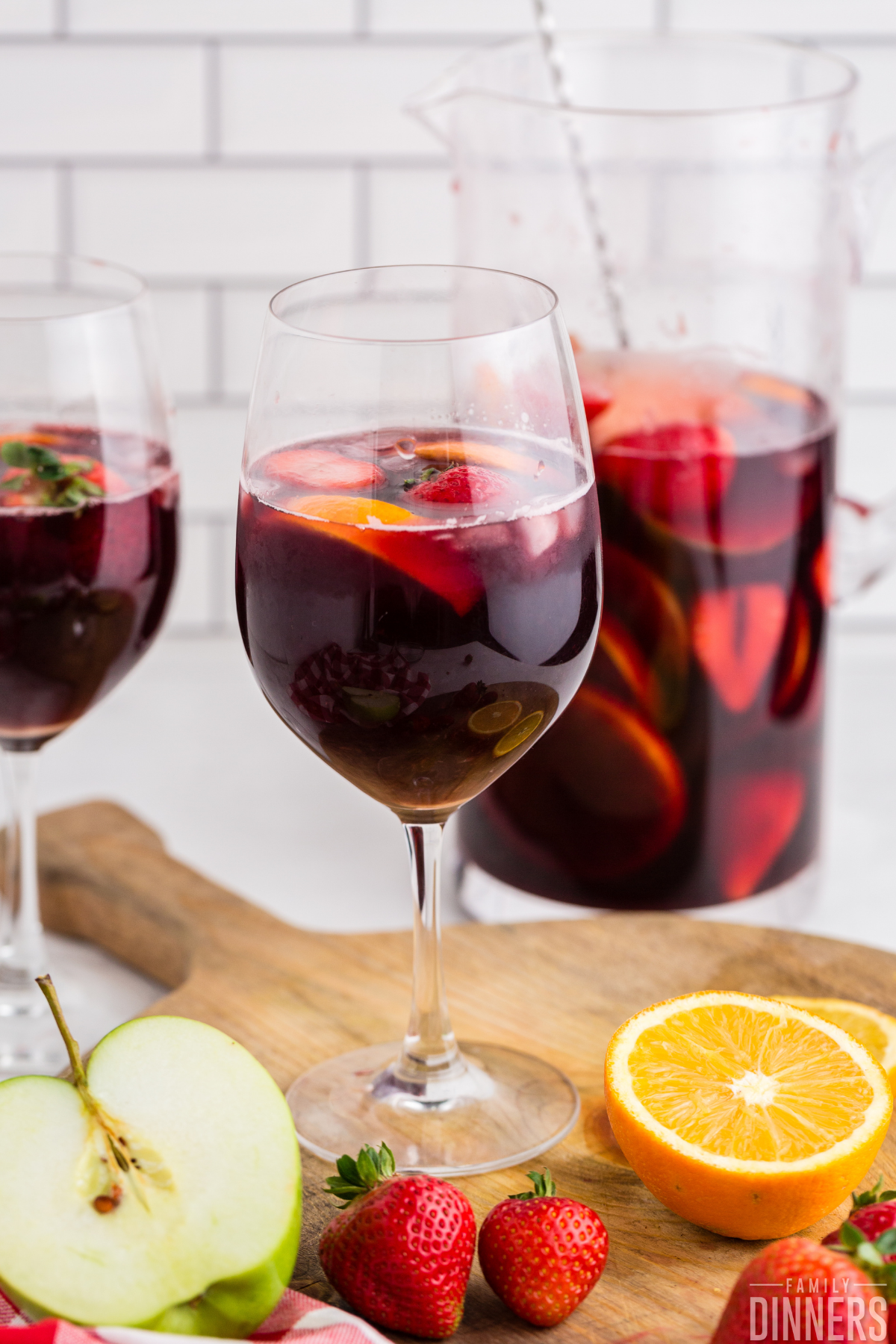 two wine glasses full of red wine sangria with oranges and strawberries and apples floating in them. Glass pitcher in background full of red wine sangria and fruit