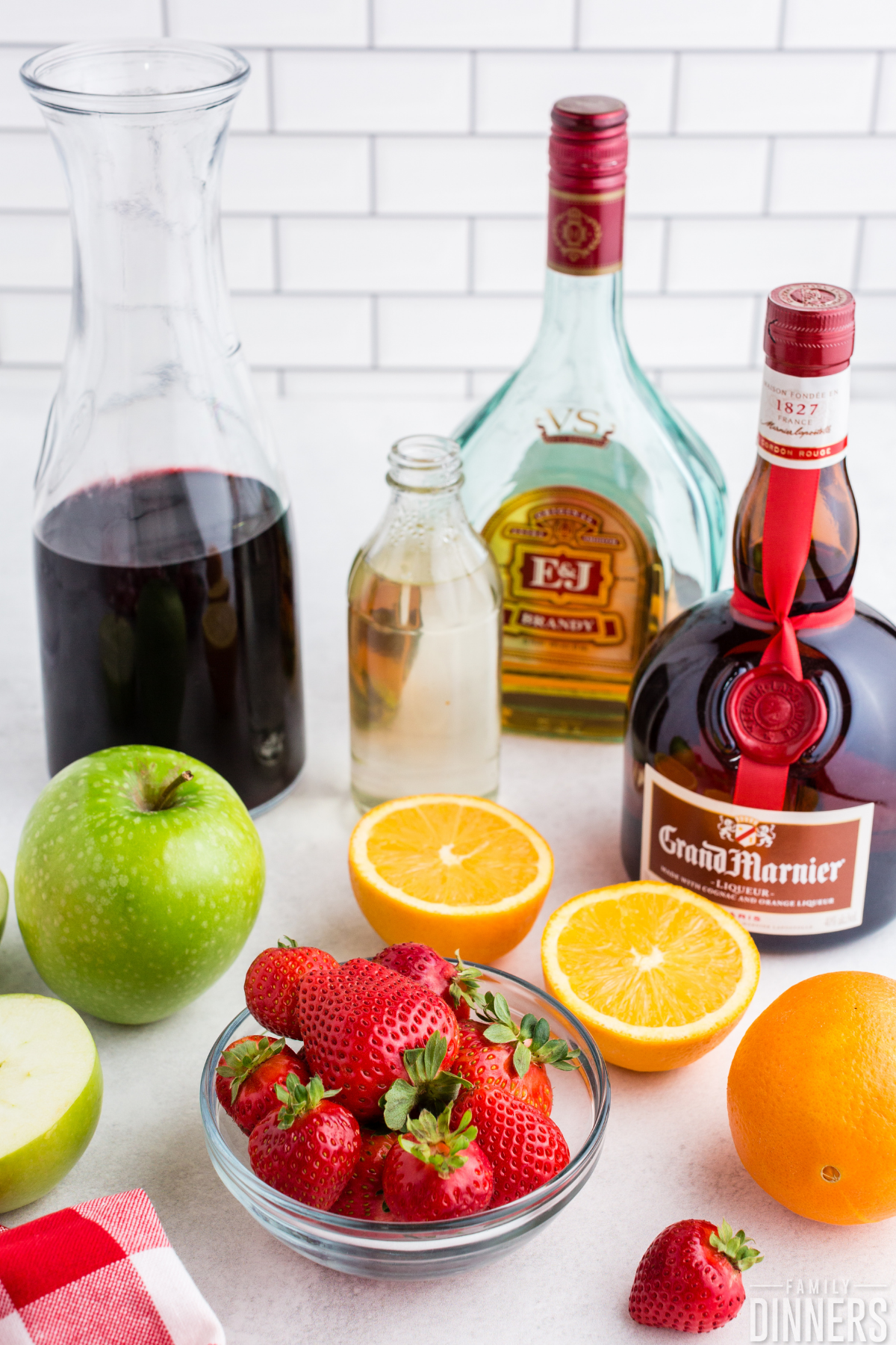 red wine sangria ingredients - grand marnier, brandy, simple syrup, red wine, apple, orange, strawberries on white counter with white subway tile backgroundw