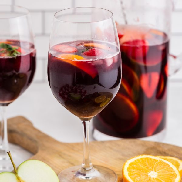 red wine sangria in wine glasses with pitcher in background and sliced apples and oranges on cutting board