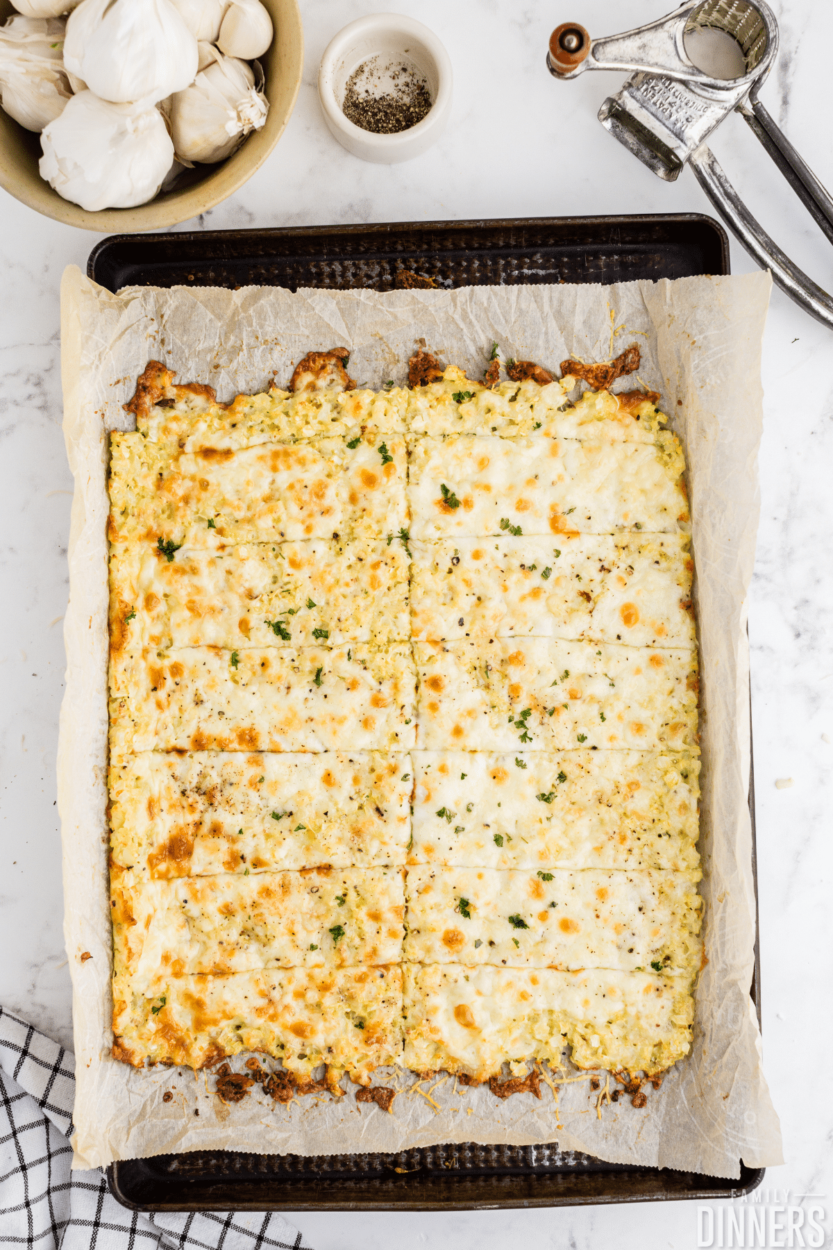 sliced cauliflower breadsticks on baking sheet