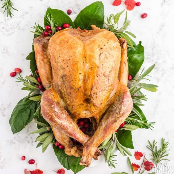 golden roasted turkey on a bed of greens and red cranberries and rosemary and sage