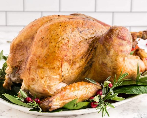 recommended recipe: dry brine turkey - image of golden roasted turkey on bed of greenery on white platter. white subway tile in the background