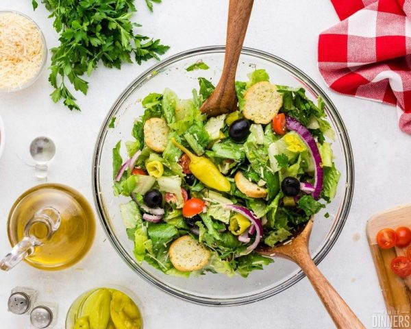 recommended recipe italian salad. Image of clear glass bowl with salad and croutons, red onion, olives. small tomatoes with wood salad tongs