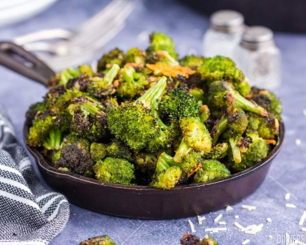 recommended recipe parmesan roasted broccoli. Image of black cast iron pan overflowing with roasted broccoli