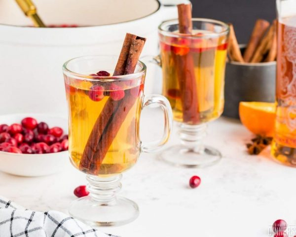 recommended hot apple cider in clear mugs with cranberries and cinnamon sticks in mugs. Bowl of red cranberries in background with bowl of cinnamon sticks, orange and alcohol