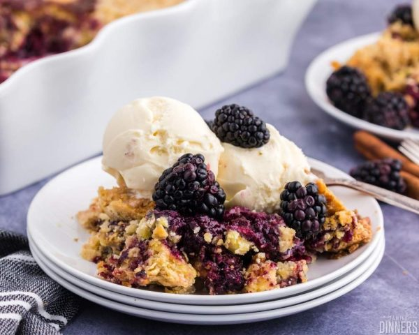 stack of white plates with serving of blackberry dump cake on top of plate with scoop of vanilla ice cream on top