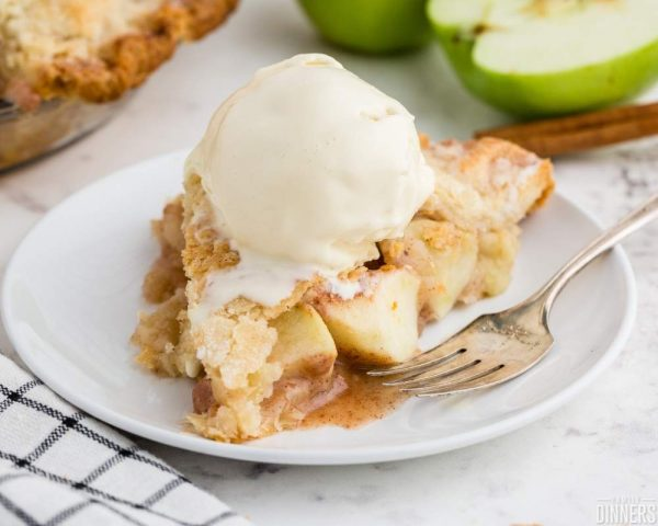 recommended recipe: granny smith apple pie. Image of white marble counter with white round plate. Slice of apple pie with round scoop of ice cream on top.
