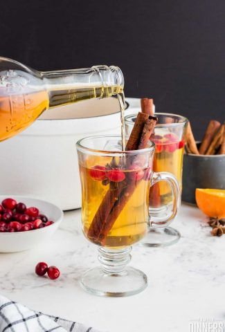 two clear glass mugs filled with golden apple cider cocktail with cranberries, cinnamon sticks in them. Bottle of Tuaca pouring into one mug..