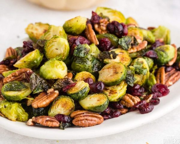 recommended recipe: roasted brussels sprouts. Image of white oval plate with golden roasted brussels sprouts with pecans and dried cranberries