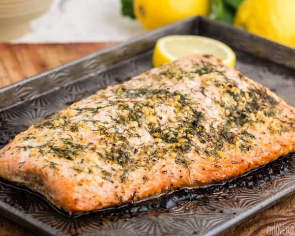 recommended recipe: baked salmon with lemon - image of salmon being flaked with a fork on a black dish
