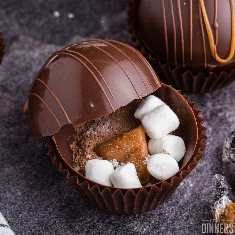 close up of an open chocolate sphere with hot cocoa mix, mini marshmallows, and a chunk of caramel visible inside