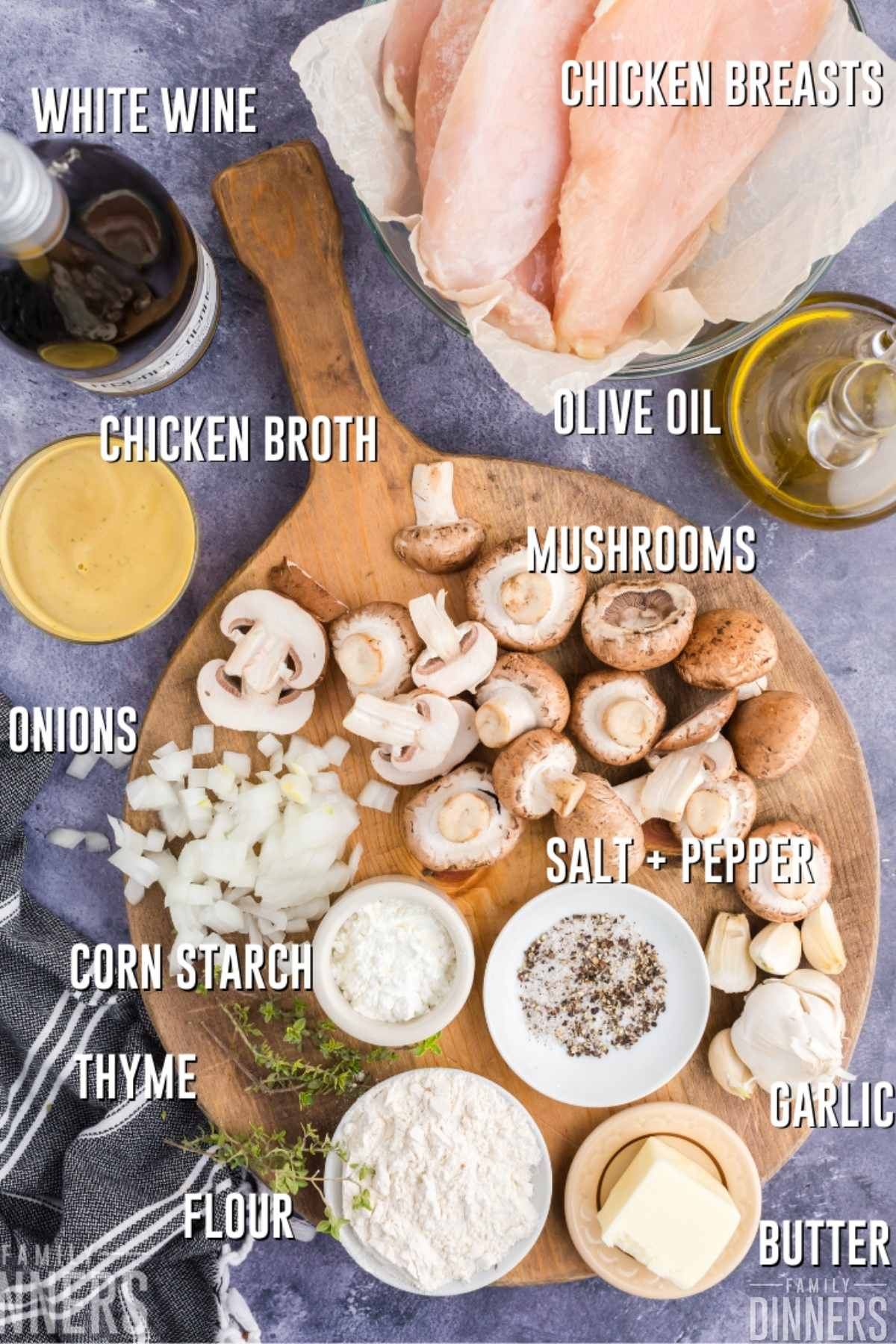 ingredients laid out on round cutting board: mushrooms, cut white onions, corn starch in small bowl, flour in small bowl, spices in small bowl, stick of butter, chicken broth in a bowl, white wine, olive oil and a bowl of raw chicken breasts