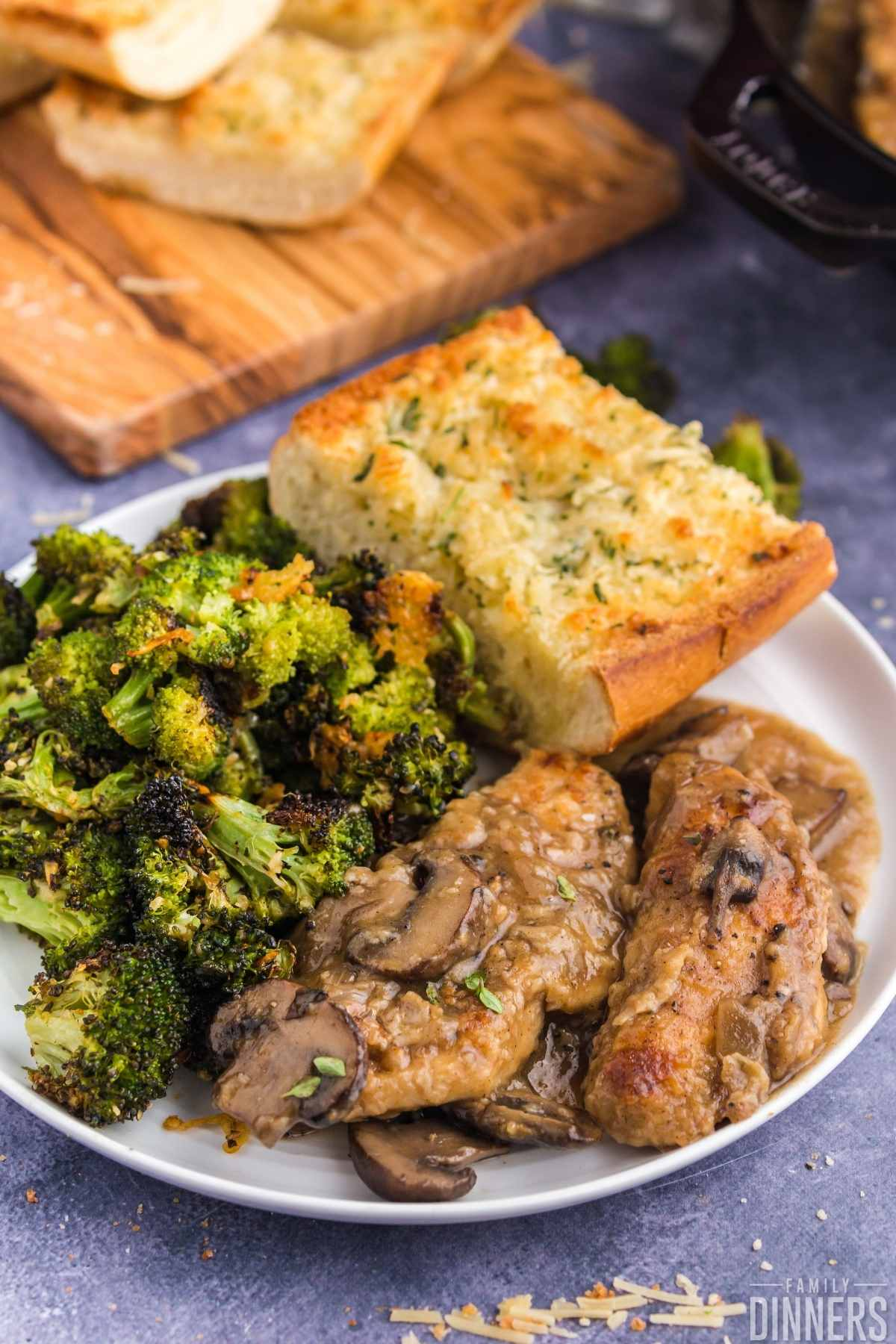white round plate full of chicken and mushrooms, roasted broccoli and parmesan french bread