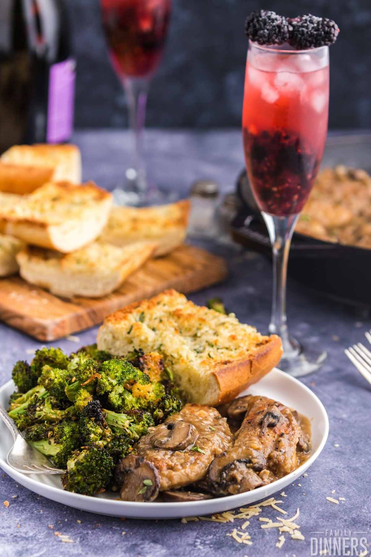 white round plate full of chicken and mushrooms, roasted broccoli and parmesan french bread with champagne glass full of blackberry cocktail