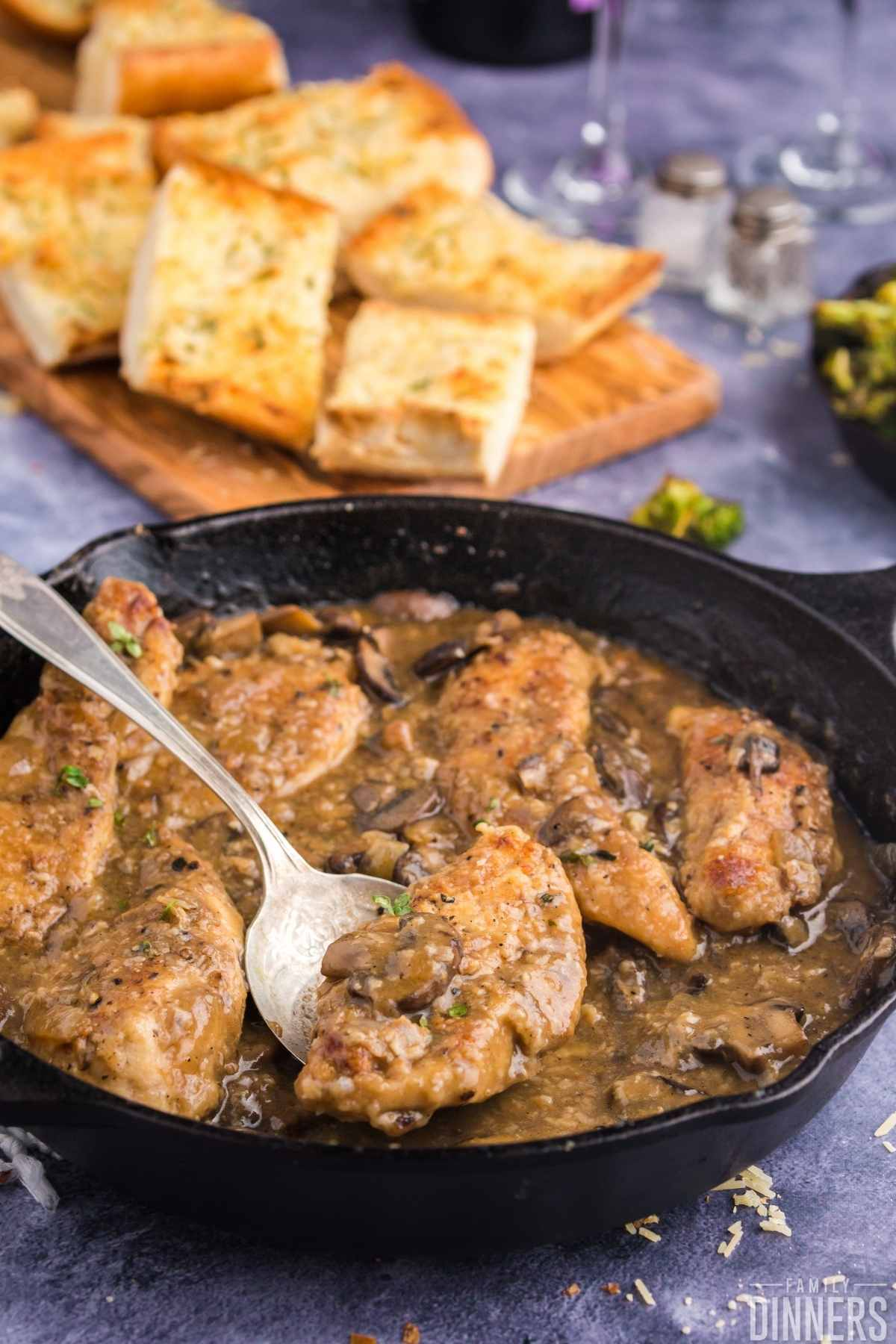 Golden cooked chicken surrounded by mushroom sauce in black cast iron pan. Golden baked french bread slices in background.
