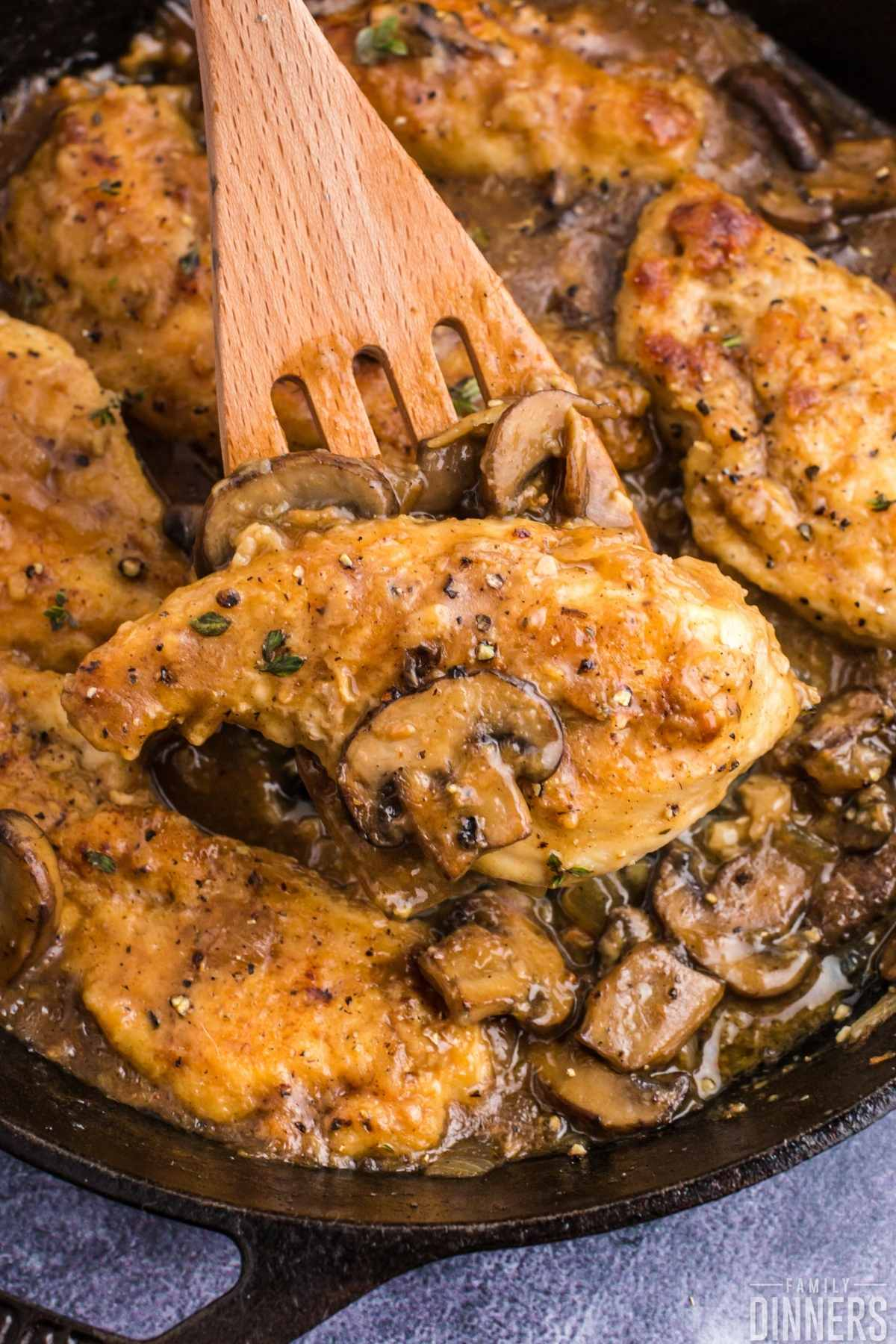 Golden cooked chicken surrounded by mushroom sauce in black cast iron pan.