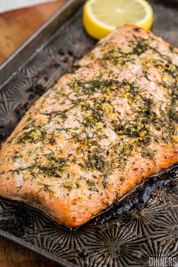 baked salmon with lemon dill butter being flaked with a fork
