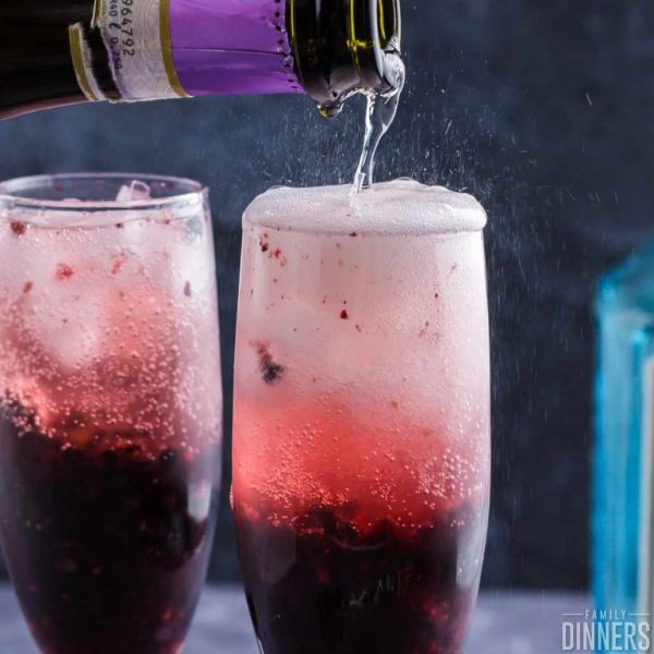 champagne being poured into two champagne glasses full of blackberry puree in bottom of glass. Bubbles foaming out of top of glass