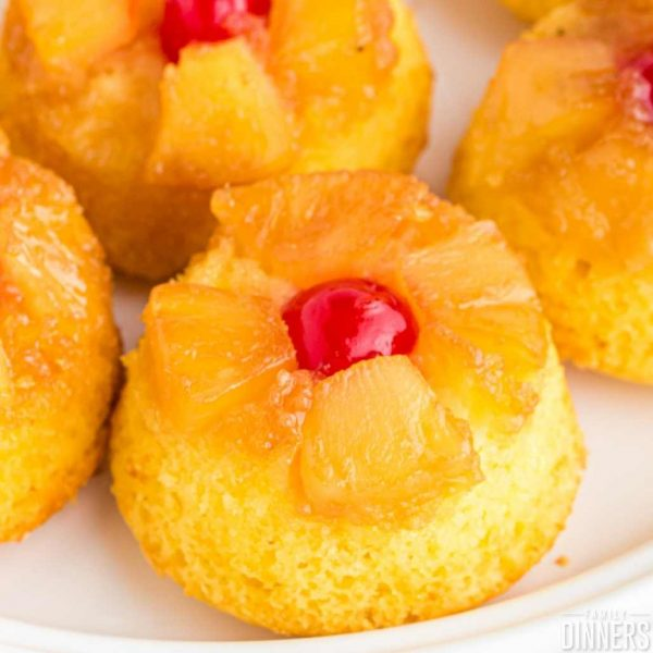 pineapple upside down mini cakes on a white plate. Red cherry on top.