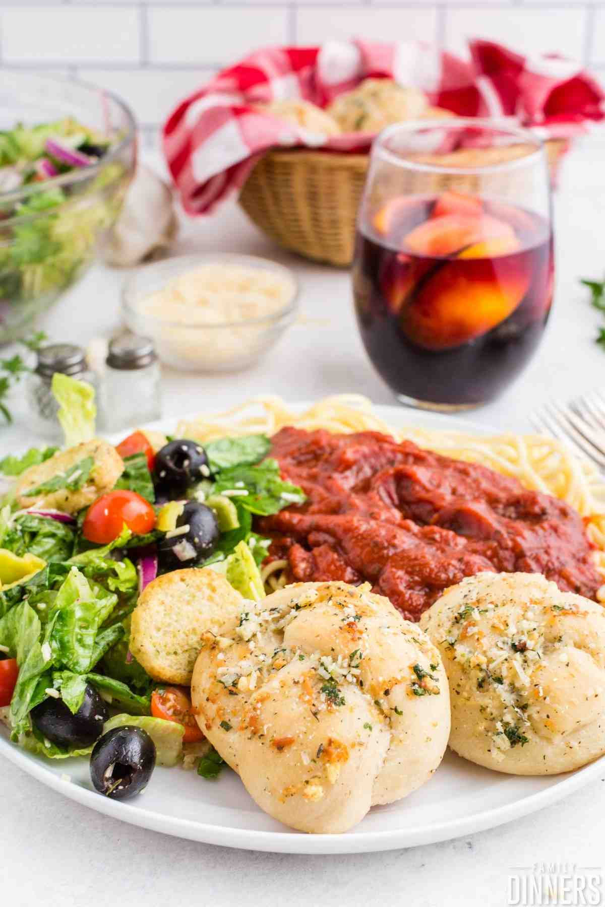 plate full of italian meal with salad, spaghetti, garlic knots and sangria.